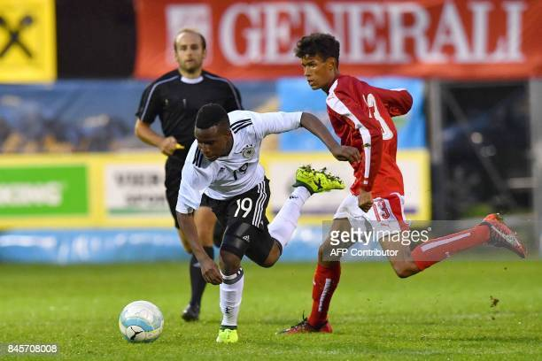 Germany's 12yearold Youssoufa Moukoko and Austria's Simon Nosa Nelson vie for the ball during the friendly U16 football match between Austria and...