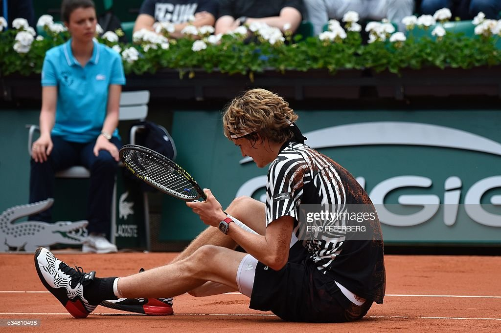 Germany's Alexander Zverev sits on the court after falling during his third round match against Austria's Dominic Thiem at the Roland Garros 2016 French Tennis Open in Paris on May 28, 2016. / AFP / Eric FEFERBERG