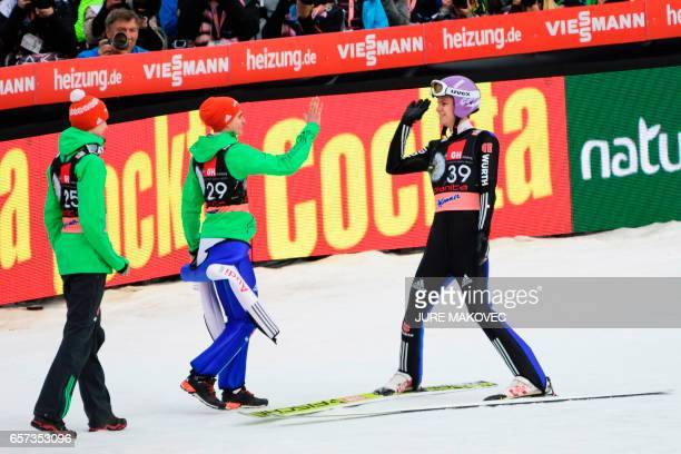 Germany's Andreas Wellinger celebrates with teammates Richard Freitag and Karl Geiger during the FIS Ski Jumping World Cup Flying Hill Individial...