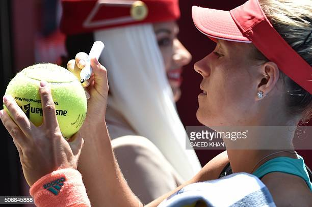 Germany's Angelique Kerber signs autographs to fans following her win against Germany's Annika Beck in their women's singles game on day eight of the...