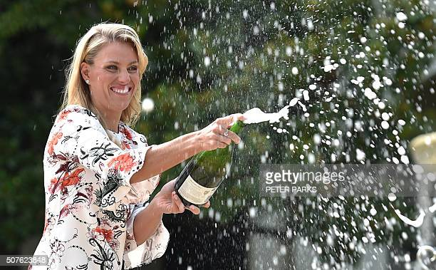 Germany's Angelique Kerber sprays champagne as she poses with The Daphne Akhurst Memorial Trophy as she celebrates her victory in the women's singles...