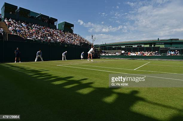 Germany's AnnaLena Friedsam serves to Switzerland's Belinda Bencic during their women's singles second round match on day three of the 2015 Wimbledon...
