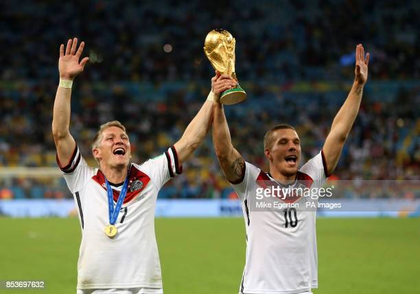 Germany's Bastian Schweinsteiger and Lukas Podolski celebrate winning the World Cup after the FIFA World Cup Final at the Estadio do Maracana Rio de...