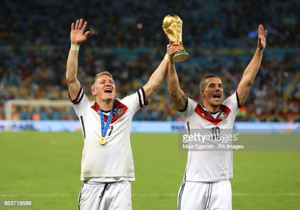 Germany's Bastian Schweinsteiger and Lukas Podolski celebrate with the World Cup trophy