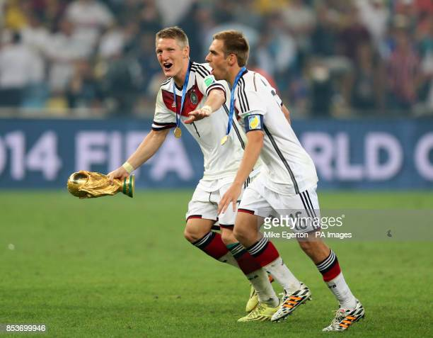 Germany's Bastian Schweinsteiger and Philipp Lahm and the World Cup trophy after the FIFA World Cup Final at the Estadio do Maracana Rio de Janerio...