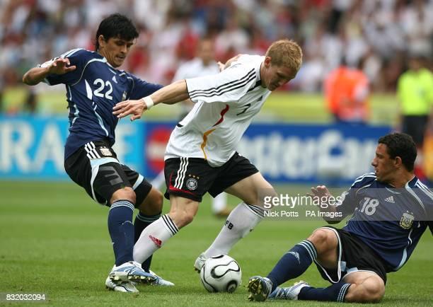 Germany's Bastian Schweinsteiger battles with Argentina's Lucho Gonzalez and Rodriguez Maxi