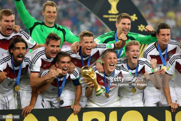 Germany's Bastian Schweinsteiger celebrates with the FIFA World Cup Trophy and teammates after winning the FIFA World Cup Final at the Estadio do...