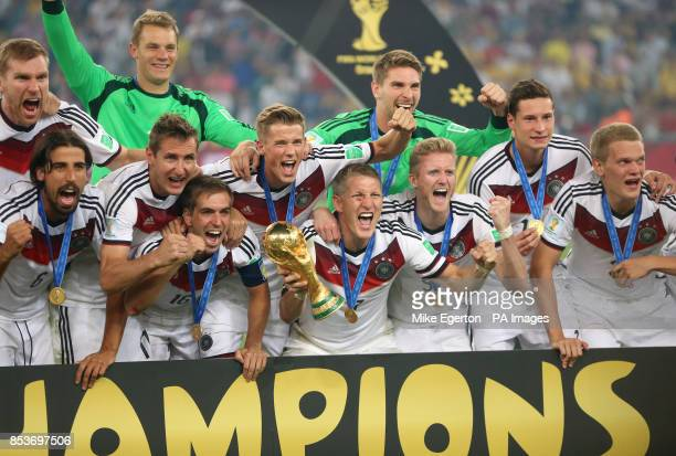 Germany's Bastian Schweinsteiger celebrates with the World Cup trophy and teammates after winning the World Cup in the FIFA World Cup Final at the...