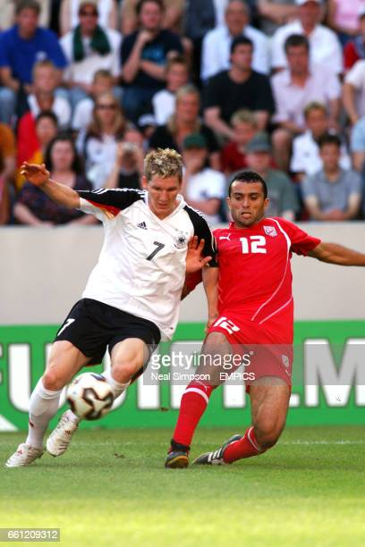 Germany's Bastian Schweinsteiger holds off a challenge from Tunisia's Jawhar Mnari