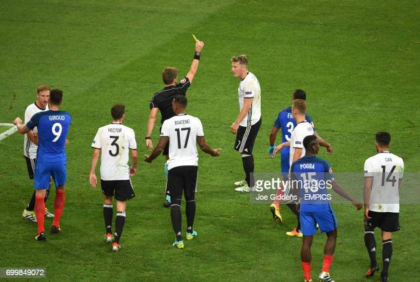 Germany's Bastian Schweinsteiger is shown a yellow card by match referee Nicola Rizzoli after handling the ball