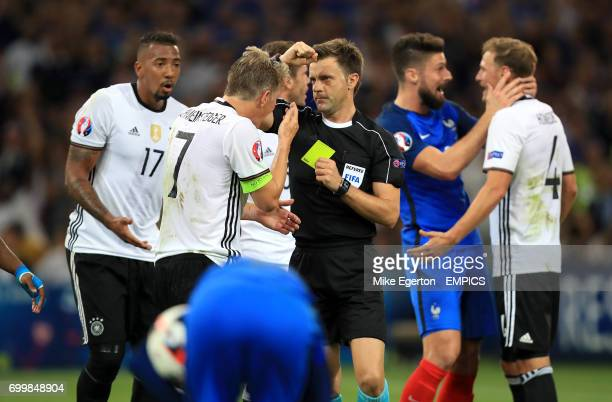 Germany's Bastian Schweinsteiger is shown a yellow card by referee Nicola Rizzoli for handball resutling in a penalty to France
