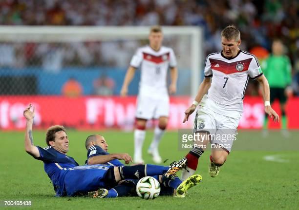 Germany's Bastian Schweinsteiger is tackled by Argentina's Lucas Biglia and Javier Mascherano