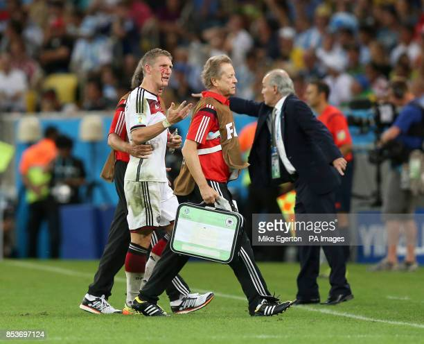 Germany's Bastian Schweinsteiger walks off the pitch after receiving treatment for his bloodied face during the FIFA World Cup Final at the Estadio...