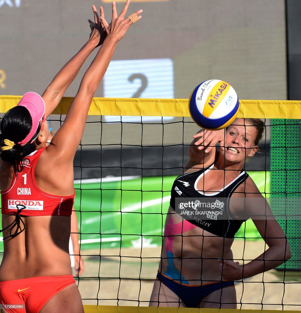 Germany's Britta Büthe (R) spikes a ball against China's Zhang Xi in the final match of the Beach Volleyball World Championships on July 6, 2013 in Stare Jablonki, Poland.