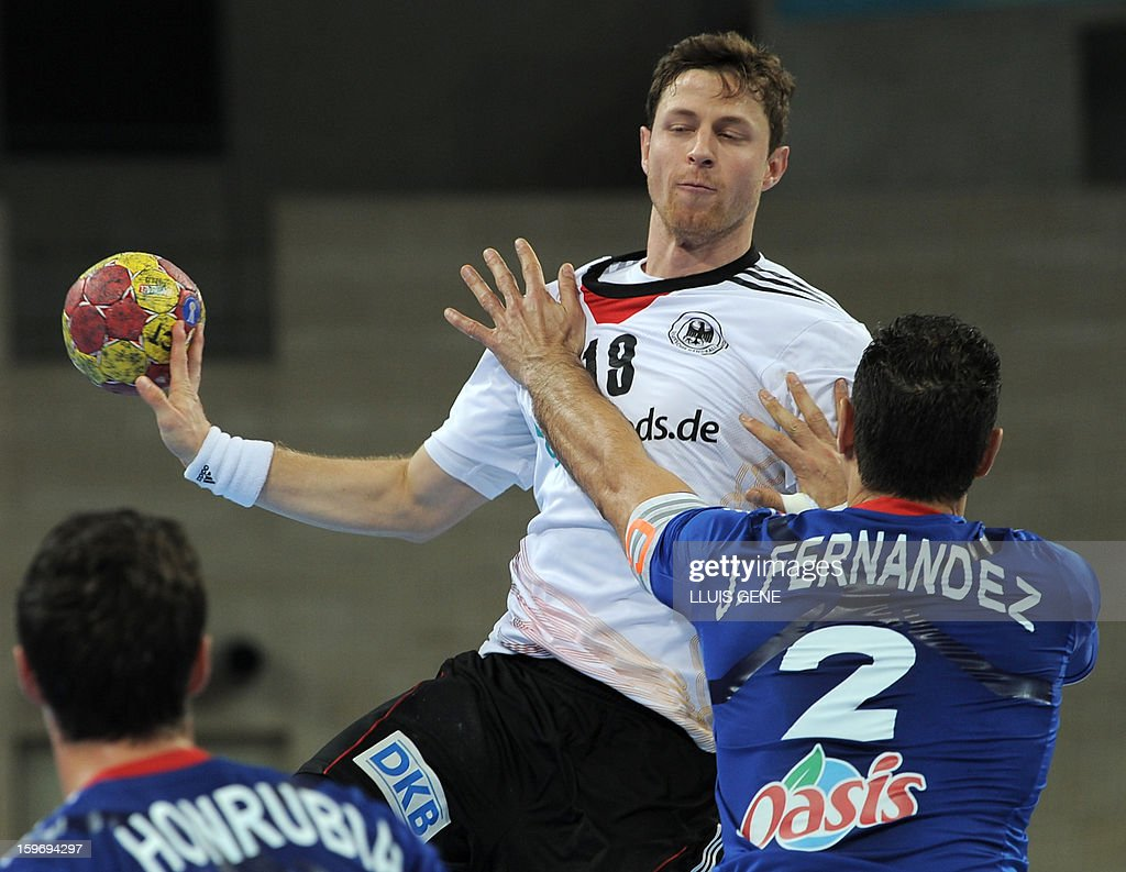 Germany's centre back Martin Strobel (L) vies with France's left wing Jerome Fernandez (R) during the 23rd Men's Handball World Championships preliminary round Group A match France vs Germany at the Palau Sant Jordi in Barcelona on January 18, 2013. AFP PHOTO / LLUIS GENE
