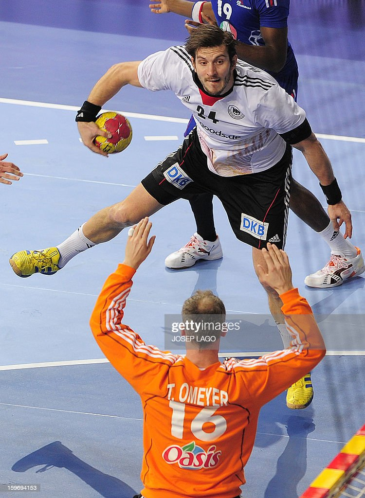 Germany's centre back Michael Haab (up) jumps tp shoot in front to France's goalkeeper Thierry Omeyer during the 23rd Men's Handball World Championships preliminary round Group A match France vs Germany at the Palau Sant Jordi in Barcelona on January 18, 2013. AFP PHOTO/ JOSEP LAGO