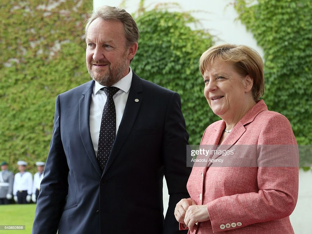Germany's Chancellor Angela Merkel (R) and Bosnian member of the Tripartite Presidency of Bosnia and Herzegovina Bakir Izetbegovic (L) pose for photographer during an official welcoming ceremony at Chancellery on June 30, 2016 in Berlin, Germany.