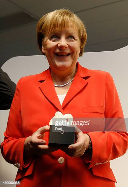 Germany's Chancellor Angela Merkel is holds a 'moodlight' designed by 11yearold Esther Shulz which she made with a 3D printer during Merkel's visit...