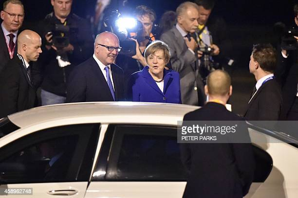 Germany's Chancellor Angela Merkel is welcomed upon her arrival at the airport in Brisbane to take part in the G20 summit on November 14 2014...