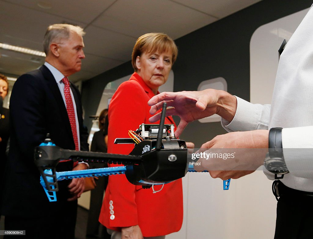 Germany's Chancellor Angela Merkel looks at a drone prototype whose electronics are designed to withstand cyber attack during Merkel's visit to the Future Logistics Living Lab on November 17, 2014 in Sydney, Australia. German Chancellor Angela Merkel is attending meetings in Sydney following the G20 Leaders Summit in Brisbane.