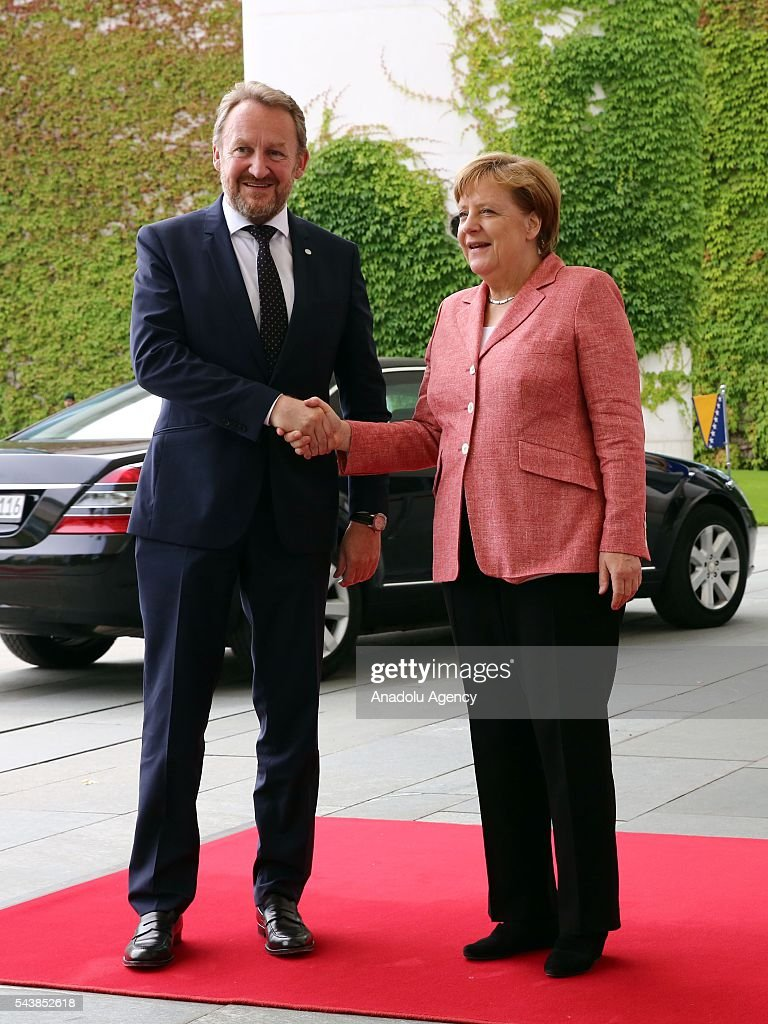 Germany's Chancellor Angela Merkel shake hands with Bakir Izetbegovic (L), Bosnian member of the Tripartite Presidency of Bosnia and Herzegovina at an official welcoming ceremony at Chancellery on June 30, 2016 in Berlin, Germany.