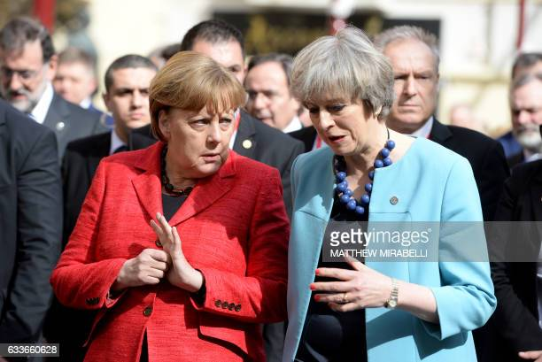 Germany's Chancellor Angela Merkel speaks with British Prime Minister Theresa May on their way for a family picture during an European Union summit...