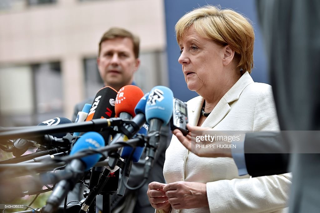 Germany's Chancellor Angela Merkel talks to journalists as she arrives before an EU summit meeting on June 28, 2016 at the European Union headquarters in Brussels. / AFP / PHILIPPE