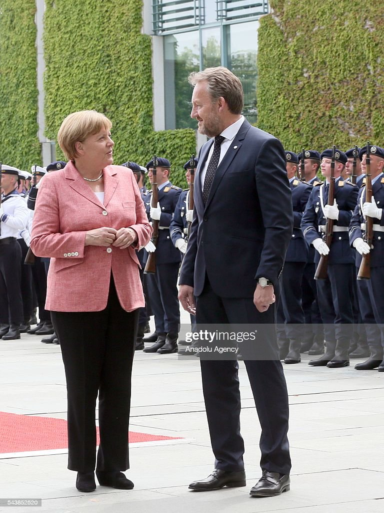 Germany's Chancellor Angela Merkel talks with Bakir Izetbegovic (R), Bosnian member of the Tripartite Presidency of Bosnia and Herzegovina at an official welcoming ceremony at Chancellery on June 30, 2016 in Berlin, Germany.