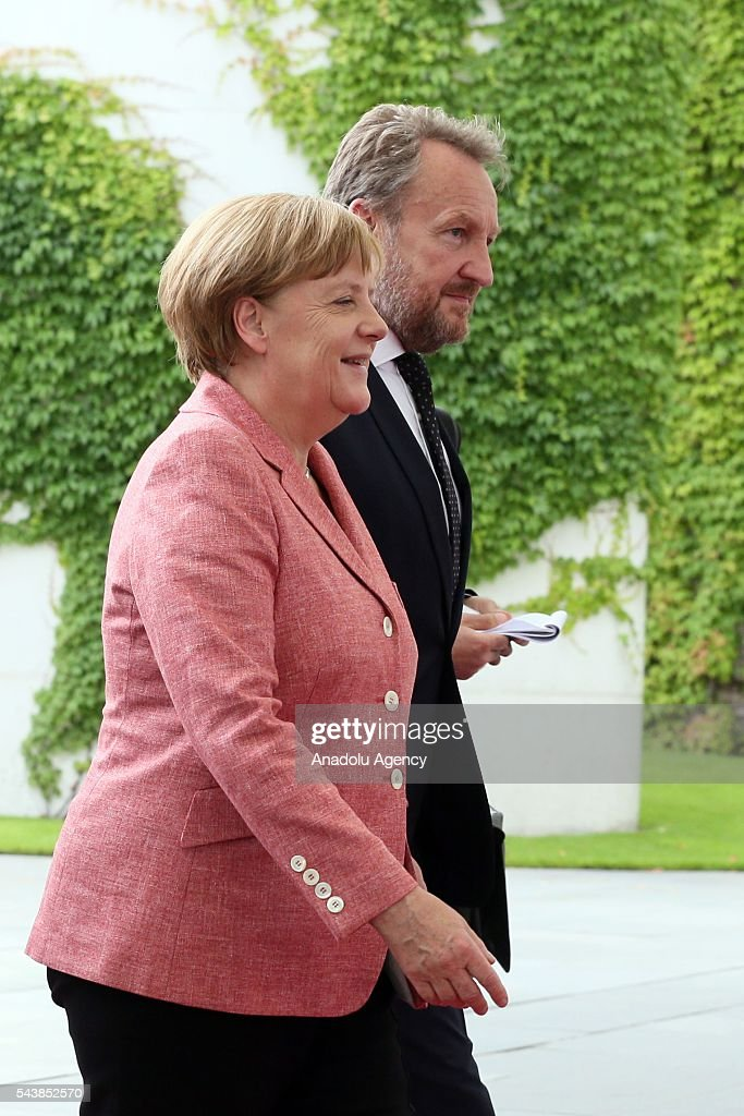 Germany's Chancellor Angela Merkel (L) welcomes Bosnian members of the Tripartite Presidency of Bosnia and Herzegovina Dragan Covic (not seen), Mladen Ivanic (not seen) and Bakir Izetbegovic (R) at an official welcoming ceremony at Chancellery on June 30, 2016 in Berlin, Germany.