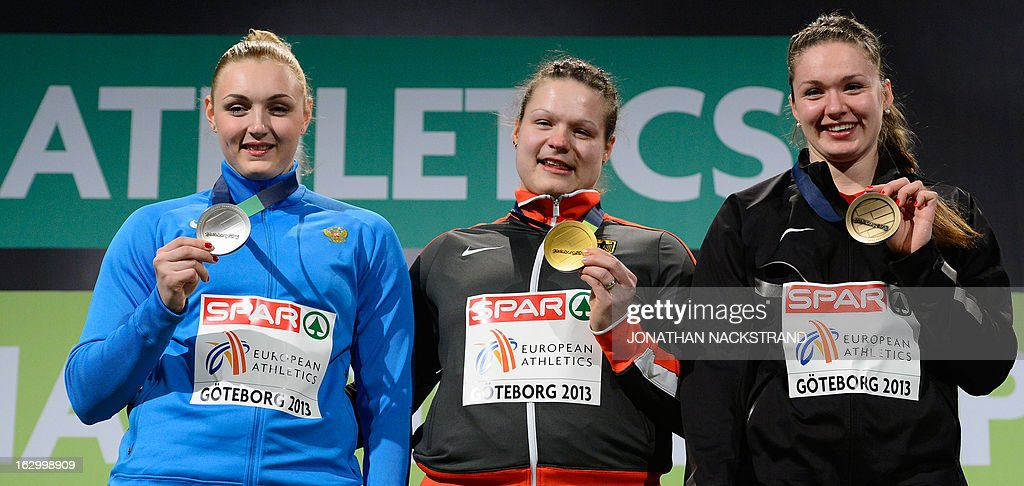 Germany's Christina Schwanitz (C) celebrates winning the Women's Shot Put final event on the podium with 2nd place Russia's Yevgeniya Kolodko (L) and 3rd place Belarus' Alena Kopets at the European Indoor athletics Championships in Gothenburg, Sweden, on March 3, 2013. AFP PHOTO / JONATHAN NACKSTRAND