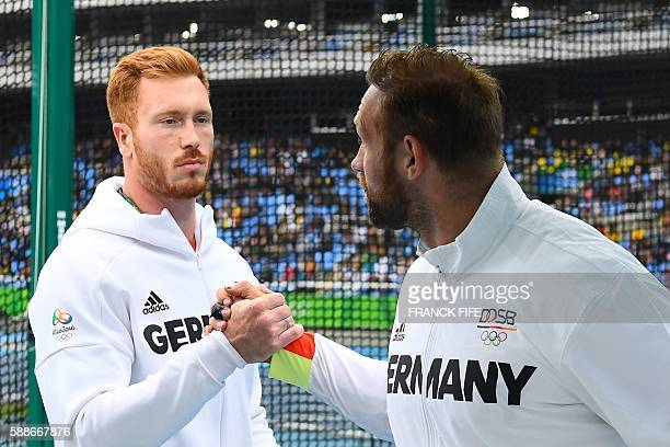 Germany's Christoph Harting shakes hands with Germany's Robert Harting in the Men's Discus Throw Qualifying Round during the athletics event at the...