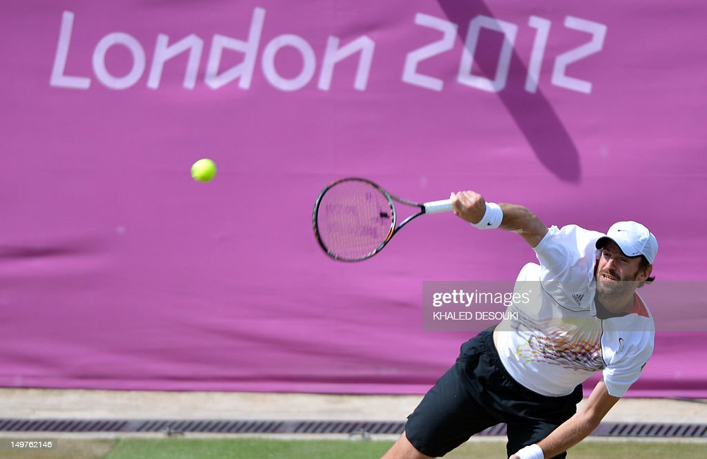 Germany's Christopher Kas serves to Italy's Roberta Vinci and Daniele Bracciali during his London 2012 Olympic Games mixed double quarter final match with teammate Sabine Lisicki at the All England Tennis Club in Wimbledon, southwest London, on August 3, 2012.