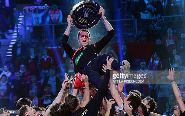 Germany's coach Dagur Sigurðsson holds the trophy as he celebrates with his players after winning the final match of the Men's 2016 EHF European...