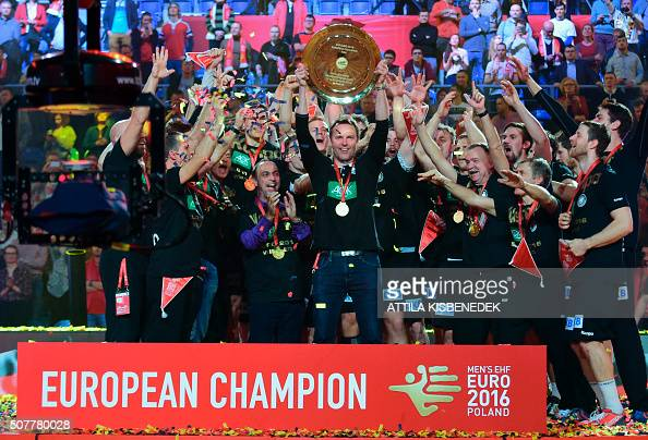 Germany's coach Dagur Sigurðsson lifts the trophy as he celebrates with his players after winning the final match of the Men's 2016 EHF European...