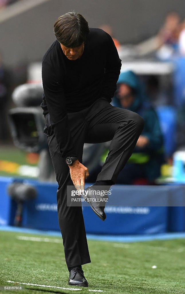 Germany's coach Joachim Loew checks his shoe during the Euro 2016 round of 16 football match between Germany and Slovakia at the Pierre-Mauroy stadium in Villeneuve-d'Ascq near Lille on June 26, 2016. / AFP / PATRIK