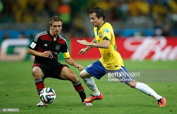 Germany's defender and captain Philipp Lahm vies withBrazil's forward Bernard during the semifinal football match between Brazil and Germany at The...