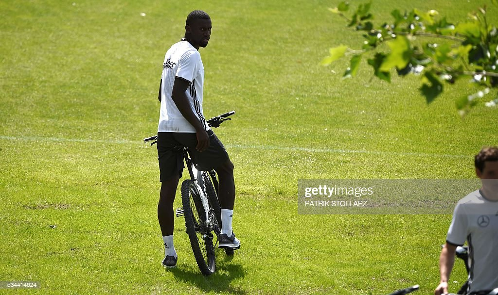 Germany's defender Antonio Ruediger sits on his bike and leaves the a training session as part of the team's preparation for the upcoming Euro 2016 European football championships, on May 26, 2016 in Ascona. / AFP / PATRIK