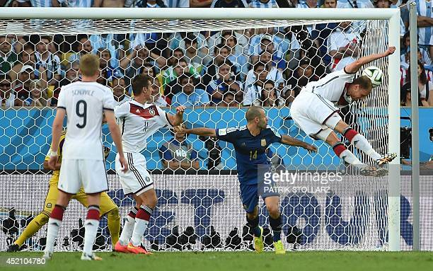 Germany's defender Benedikt Hoewedes heads the ball towards the goal as Argentina's midfielder Javier Mascherano and Germany's forward Miroslav Klose...