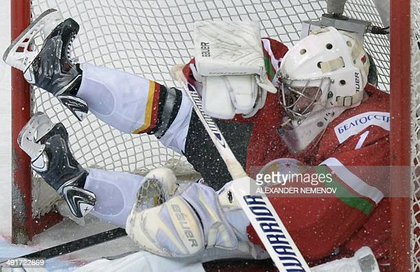 Germany's defender Benedikt Kohl falls into the net of Belarus' team during a preliminary round group B game Belarus vs Germany of the IIHF...