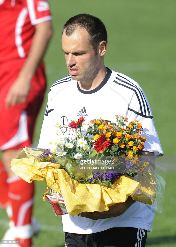 Germany's defender Heiko Westermann carries a bouquet off the pitch at the beginning of a training match Germany vs Sued Tyrol FC at the team's training centre in Appiano, near the north Italian city of Bolzano May 24, 2010. The German football team is currently taking part in a 12-day training camp in Appiano to prepare for the upcoming FIFA Football World Cup in South Africa.