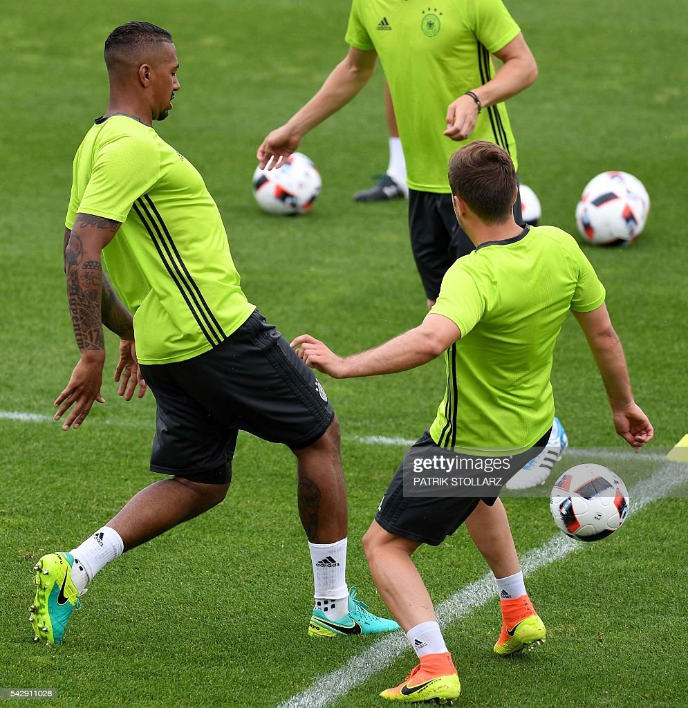 Germany's defender Jerome Boateng (L) and Germany's forward Mario Goetze (R) warm up during a training session of Germany's national football team at the team's training ground in Evian-les-Bains, south-eastern France, on June 25, 2016, on the eve of the Euro 2016 round of sixteen football match between Germany and Slovakia. / AFP / PATRIK