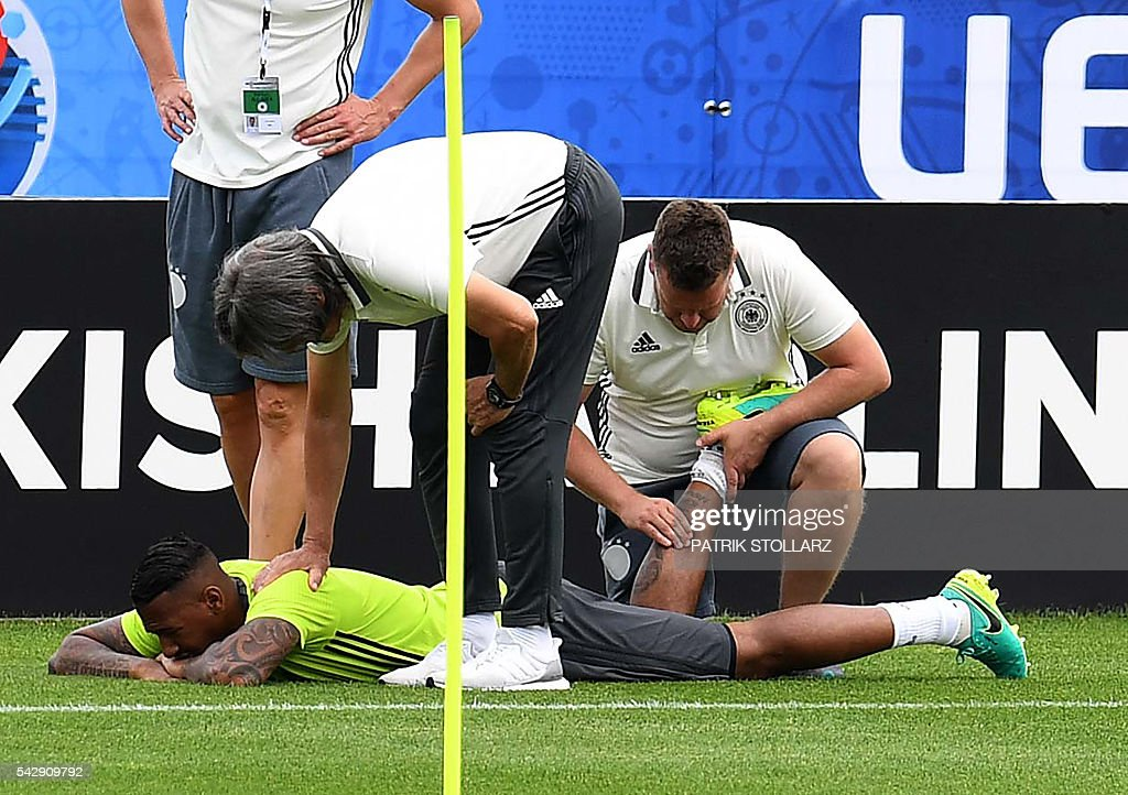 Germany's defender Jerome Boateng receives treatment from team doctor Hans-Wilhelm Mueller-Wohlfahrt during a training session of Germany's national football team at the team's training ground in Evian-les-Bains, south-eastern France, on June 25, 2016, on the eve of the Euro 2016 round of sixteen football match between Germany and Slovakia. / AFP / PATRIK