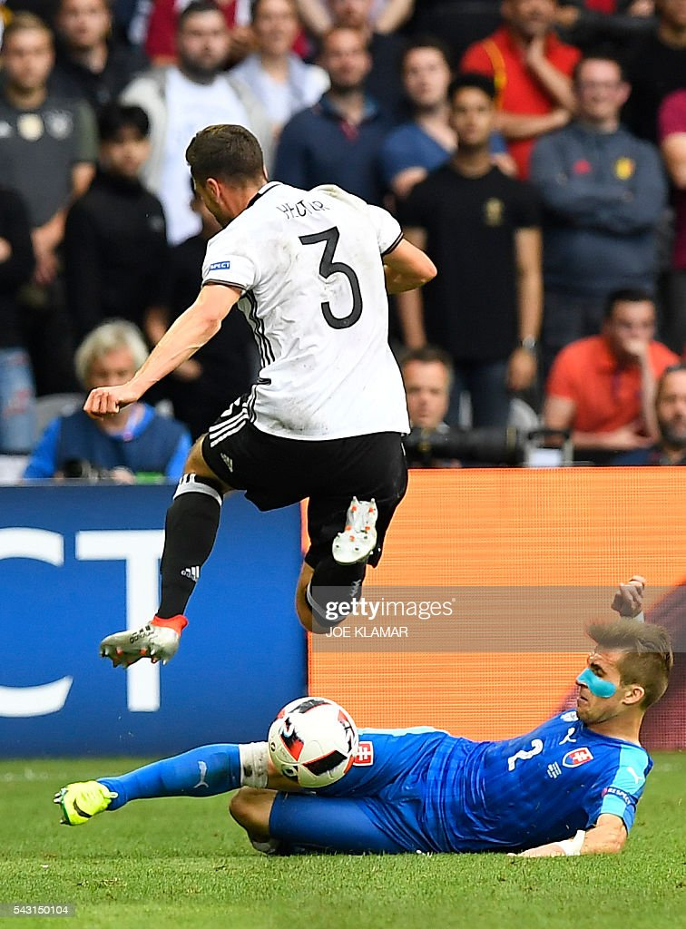 Germany's defender Jonas Hector jumps over Slovakia's defender Peter Pekarik (R) during the Euro 2016 round of 16 football match between Germany and Slovakia at the Pierre-Mauroy stadium in Villeneuve-d'Ascq near Lille on June 26, 2016. / AFP / Joe KLAMAR