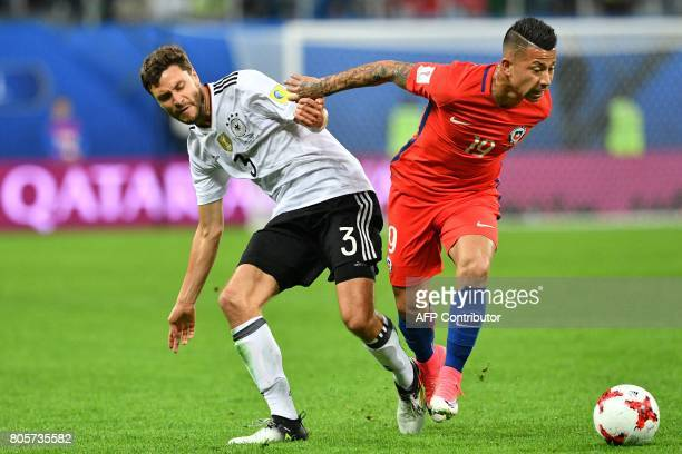 Germany's defender Jonas Hector vies with Chile's forward Leonardo Valencia during the 2017 Confederations Cup final football match between Chile and...