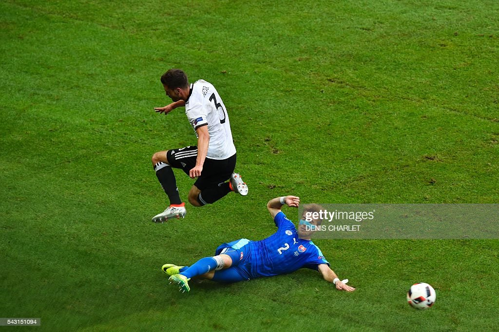 Germany's defender Jonas Hector (L) vies with Slovakia's defender Peter Pekarik during the Euro 2016 round of 16 football match between Germany and Slovakia at the Pierre-Mauroy stadium in Villeneuve-d'Ascq, near Lille, on June 26, 2016. / AFP / DENIS