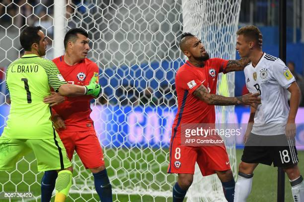 TOPSHOT Germany's defender Joshua Kimmich argues with Chile's midfielder Arturo Vidal as Chile's goalkeeper Claudio Bravo holds back Chile's defender...
