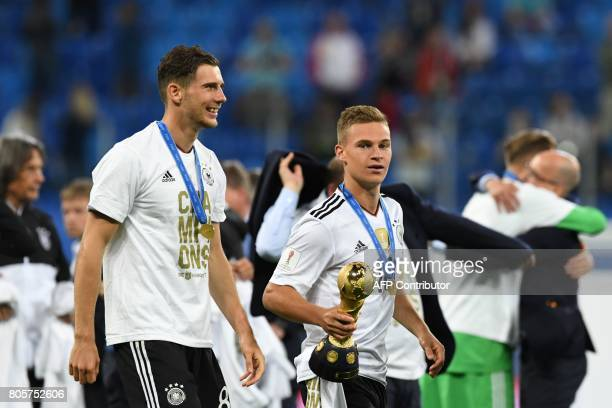 Germany's defender Joshua Kimmich holds the winner's trophy as he walks along side Germany's midfielder Leon Goretzka after they beat Chile 10 in the...