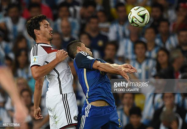 Germany's defender Mats Hummels and Argentina's forward Sergio Aguero vie for the ball during the 2014 FIFA World Cup final football match between...