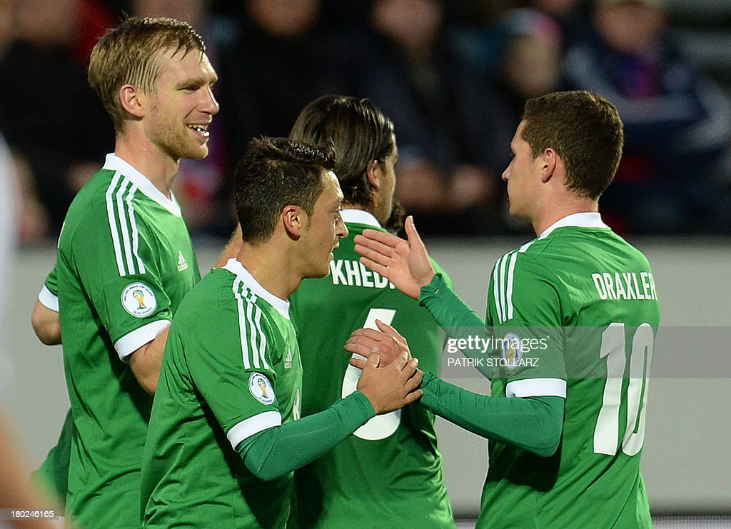 Germany's defender Per Mertesacker (L) celebrates scoring with his teammates during the FIFA World Cup 2014 qualifying football match Faroe Island vs Germany in Torshavn on September 10, 2013. AFP PHOTO / PATRIK STOLLARZ