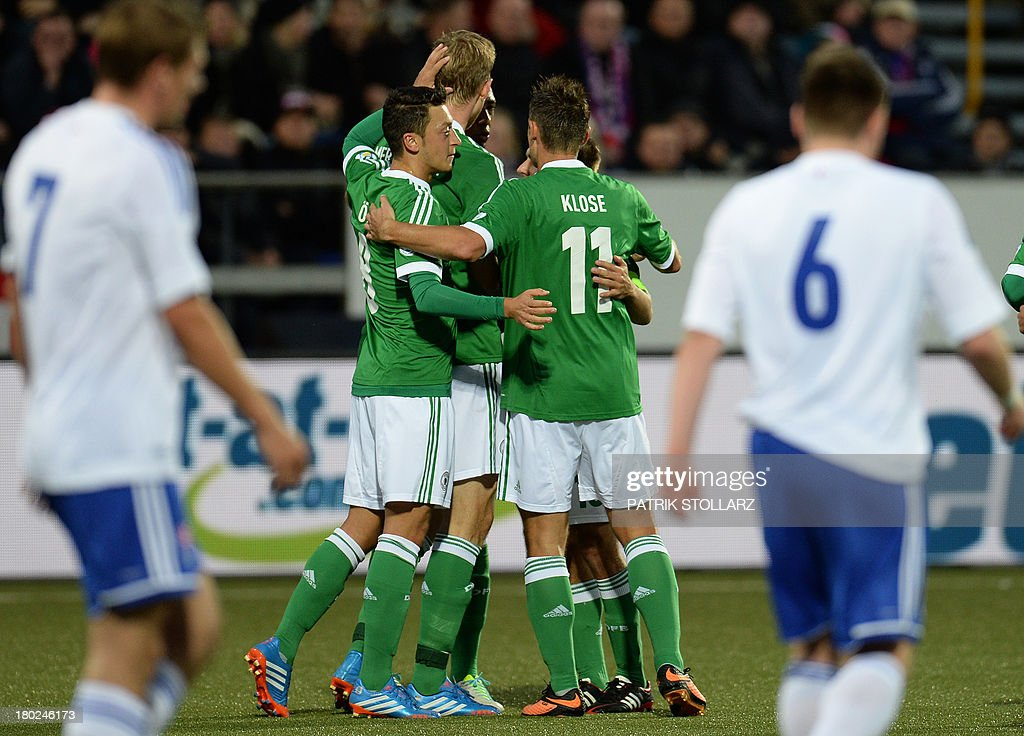 Germany's defender Per Mertesacker (2nd L) celebrates scoring with his teammates during the FIFA World Cup 2014 qualifying football match Faroe Island vs Germany in Torshavn on September 10, 2013. AFP PHOTO / PATRIK STOLLARZ